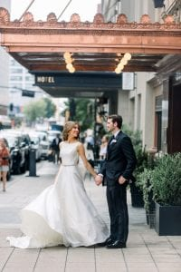 Bride wearing a full length white gown with cascading train while the groom is in a black suit on their wedding day, standing in front of the Adolphus hotel