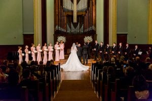 Bride, groom, and their bridesmaids and groomsmen standing at the altar of the church at their wedding ceremony