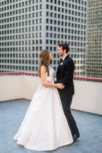 Bride and groom on their wedding day, with their arms wrapped around each other as they stand on a rooftop with a skyscraper in the background