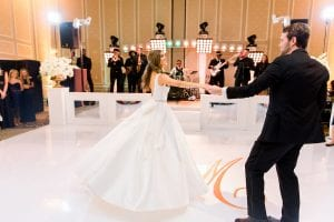 Bride and groom on a white dance floor, with a white stage and band behind them, moving to their first dance