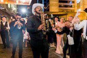 Trumpet player leading the wedding guests out of the hotel for the wedding exit