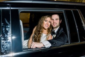 Bride and groom smiling as they sit in their getaway car, ready to drive off
