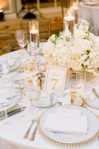 White floral centerpieces on a guest table with beaded gold chargers, glassware and flatware