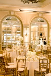 White floral centerpieces on a guest table with beaded gold chargers, glassware and flatware, with other guest tables and the cake table behind it, with mirrored glass in the background