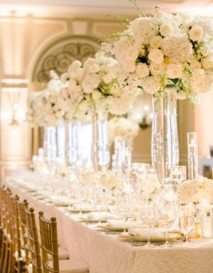 Tall white centerpieces on the head table, filled with glassware and gold beaded chargers, and gold chiavari chairs in a ballroom uplit with amber uplighting