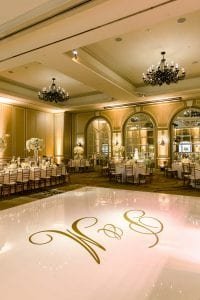White monogrammed dance floor with the head table and other guest tables surrounding it