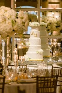 Five tiered white cake with gold monogram and clusters of white floral, with a mirrored background at the ballroom of The Adolphus hotel