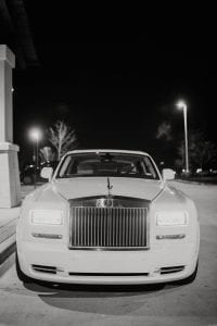 White Rolls Royce waiting in the driveway with the lights on