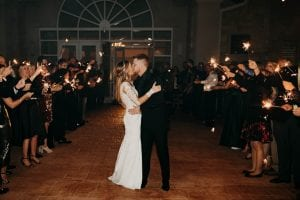 Bride and groom pausing to kiss as they exit the wedding venue, as their guests hold sparklers on either side of them