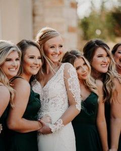 Bride and bridesmaids smiling at the camera