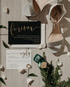 Black and white wedding stationery suite with gold foil, ring box, bride's shoes and pine leaves and ivory flower petals