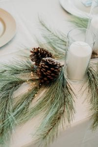 Table set up at a wedding with candles and pine cones, and fir sprigs as table decor