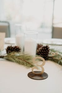 Table number set up at a wedding with candles and pine cones, and fir sprigs as table decor