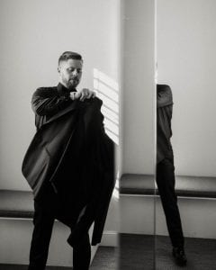 Groom putting on his suit jacket in front of a mirror