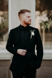 Groom wearing all black with a white boutonniere, looking off in the distance