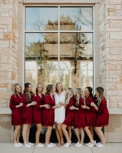 Bride in a white bathrobe while bridesmaids are in red bathrobes, smiling at each other