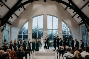 Bride, groom and their bridal party standing at the altar as the officiant speaks, and guests look on