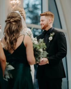 Groom looking at the officiant as he stands at the altar