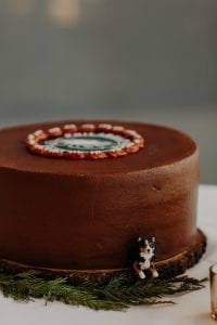 Round groom's cake made of chocolate with a little dog figurine on one side