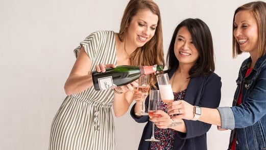 Smiling women pouring pink champagne into flutes