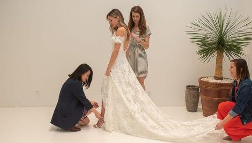 Three women helping a bride in her wedding dress