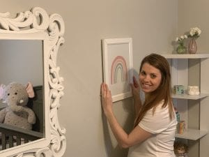 Smiling woman putting up a rainbow picture in a nursery