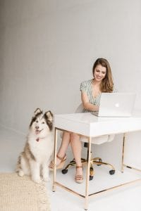 Smiling woman sitting on an ivory rolling office chair, typing on a macbook air on a sleek white desk while a brown and white Siberian Husky sits by her side