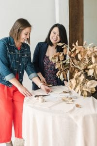 Two smiling women arranging a stationery suite, hovering over a table with blush linen