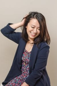 Smiling Asian woman holding her hair wearing a navy blazer over a floral print dress with gold elephant necklace