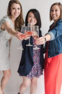 Three smiling women toasting the camera with pink champagne flutes