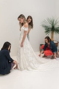 Three women helping a bride in her wedding dress