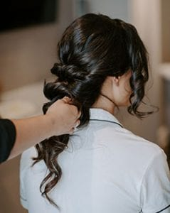 Woman's hair being braided as she sits in a white pajamas set