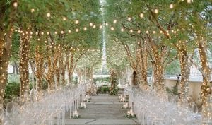 Set up of a wedding ceremony at Marie Gabrielle with clear acrylic ghost chairs within a grove of trees with string lights hanging and more lights wrapped around the base of each tree with a floral arch in the front