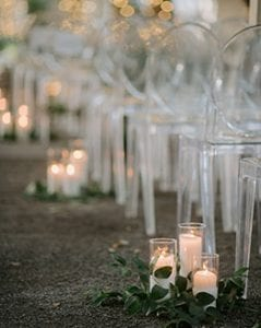 Clear acrylic ghost chairs set up for a ceremony, with candles and greenery clusters lining the pathway