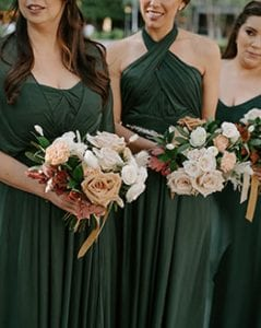 Three bridesmaids in emerald green carrying their bouquets