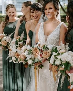 Bride and her bridesmaids on their way to the ceremony laughing and carrying their bouquets The bridesmaids are in emerald green