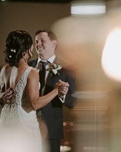 Bride and groom smiling at each other during their private last dance during their reception in Marie Gabrielle