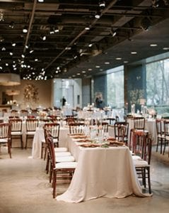 A wedding reception setup at Marie Gabrielle with white linens and brown bistro chairs