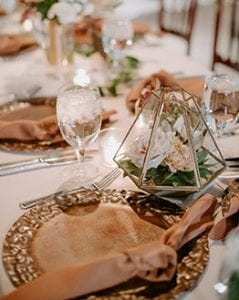 Metal charger plates with rust napkins on a white linen, with geometric centerpieces, glassware and flatware
