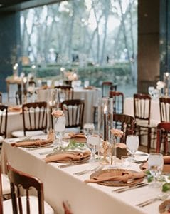 A wedding reception setup at Marie Gabrielle with white linens and brown bistro chairs There are brown charger plates and rust napkins on the table settings with glassware