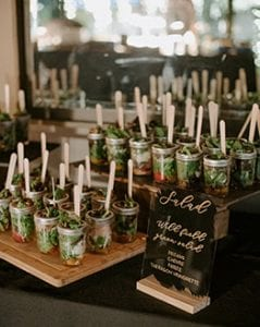 Salad on display in mason jars, set on a tiered shelf with a handwritten black menu base in gold calligraphy on its side