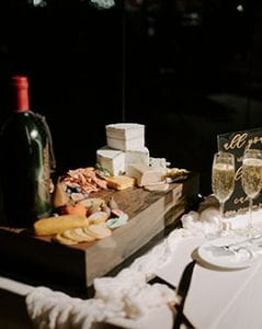 Groom's cake made to look like a charcuterie board with wine, cheese and crackers, sitting on a table with two filled champagne flutes