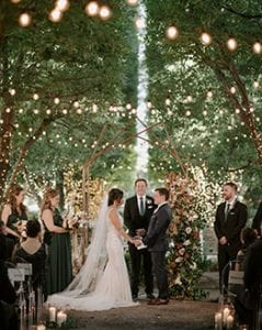 Bride and groom standing at the altar with their bridal party and officiant, under a grove of lit trees and string lights attached from one end to another, in front of a metal and floral arch