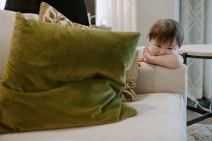 Young asian toddler with her face in her arm looking off, while leaning on a white couch with green throw cushion
