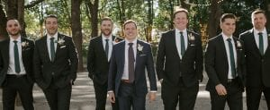 Groom and his groomsmen in their tuxes walking towards the ceremony smiling