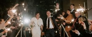 Bride wearing a white fur walking down the stairs with a waving groom as guests stand in the background waving sparklers for the wedding exit