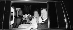 Bride and groom smiling and waving goodbye to guests as they are ready to speed off in the getaway car post wedding
