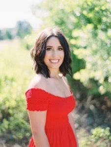 Smiling headshot of a brunette with brown eyes standing in front of a green backdrop, wearing an off shoulder red dress