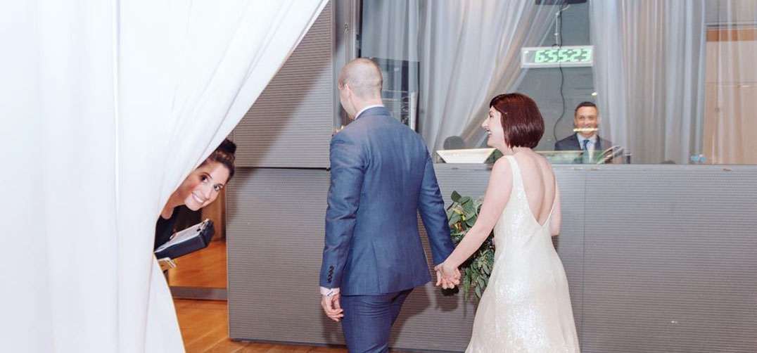 Woman peeks over drapery as bride and groom walk past her laughing