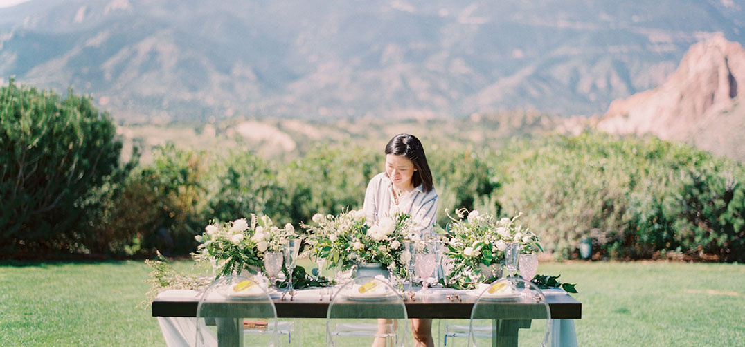 Smiling Asian woman arranging flowers on a table outdoors with the mountains in the background